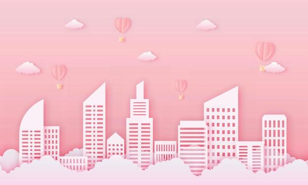 Carta tagliata felice concetto di san valentino. edificio urbano con mongolfiere a forma di cuore e nuvole che volano sul cielo rosa