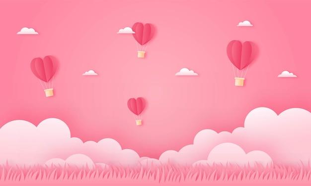 Carta tagliata felice concetto di san valentino. paesaggio con mongolfiere a forma di cuore e nuvole che volano sul cielo rosa