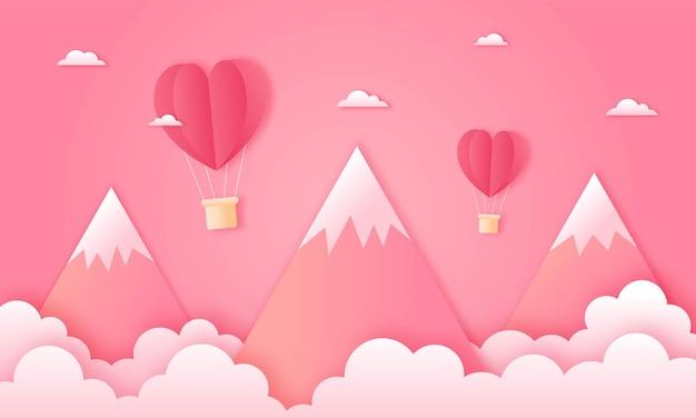 Carta tagliata felice concetto di san valentino. paesaggio con nuvole, montagne e mongolfiere a forma di cuore che volano sul cielo rosa