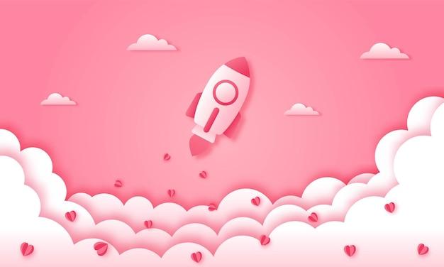 Carta tagliata felice concetto di san valentino. razzo con nuvole e cuore sul cielo rosa