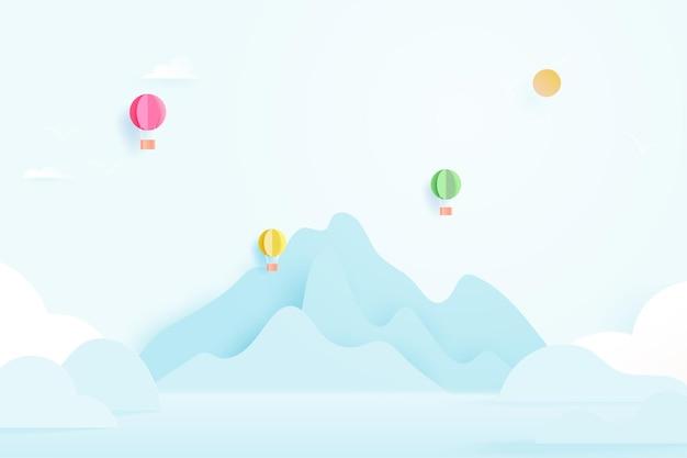 Carta tagliata di mongolfiere che volano su montagne, nuvole e cielo blu in stile arte carta pastello. illustrazione.