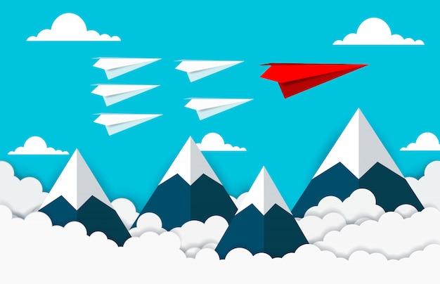 Mosca rossa e bianca dell'aereo di carta sul cielo fra la nuvola e la montagna