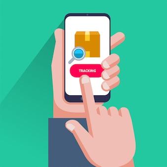 Tracciamento pacchi. passi lo smartphone della tenuta con il pacchetto del cartone, la lente d'ingrandimento e il bottone di inseguimento