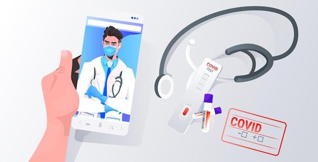 Paziente che discute con un medico maschio in maschera sullo schermo dello smartphone lotta contro la consultazione online di covid-19