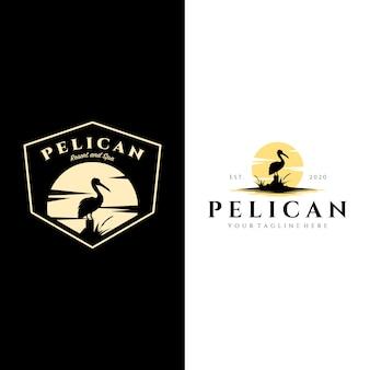 Annata di logo dell'uccello del pellicano con progettazione dell'illustrazione del fondo del sole