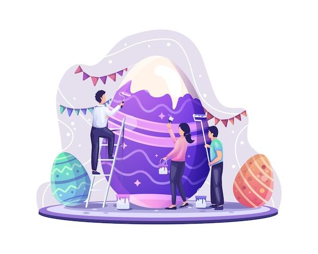 La gente celebra il giorno di pasqua decorando e dipingendo l'illustrazione gigante delle uova di pasqua