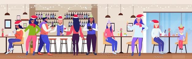 Persone che celebrano i visitatori del caffè della festa di natale in cappelli della santa che si divertono natale capodanno concetto di vacanze invernali interni del ristorante moderno