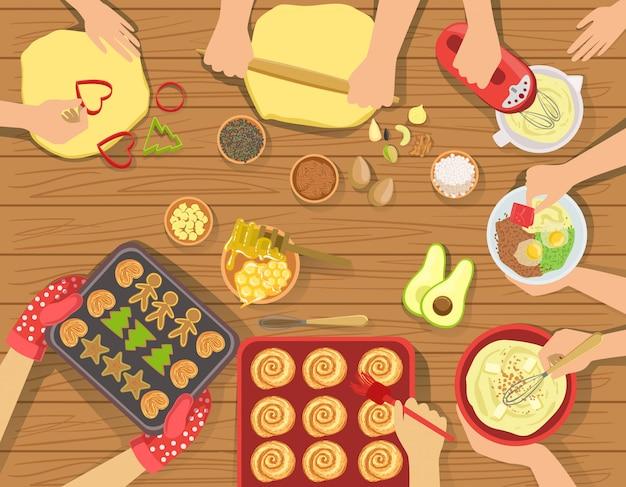 La gente che cucina insieme pasticceria e altri alimenti vista dall'alto