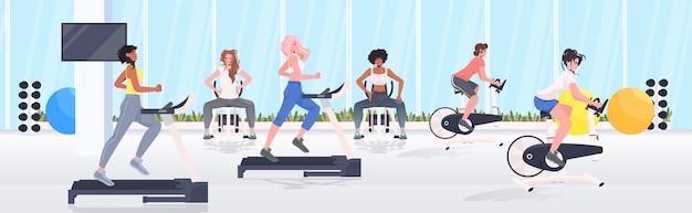 Persone che fanno esercizi fisici su apparecchi di formazione fitness allenamento concetto di stile di vita sano interni moderni della palestra