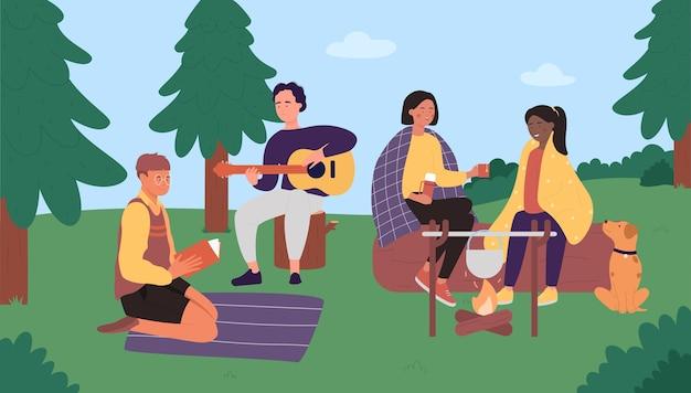 Persone amici sul campo picnic seduti vicino al fuoco, cucinando cibo divertendosi insieme