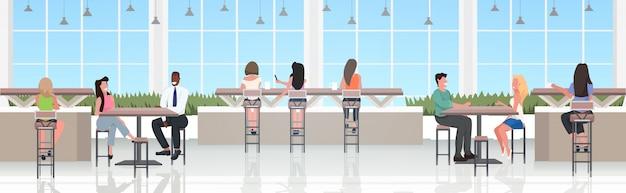 Persone sedute ai tavolini dei bar discutendo durante l'incontro moderno nel ristorante
