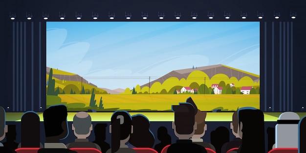 La gente che si siede nel cinema guardando la retrovisione di film
