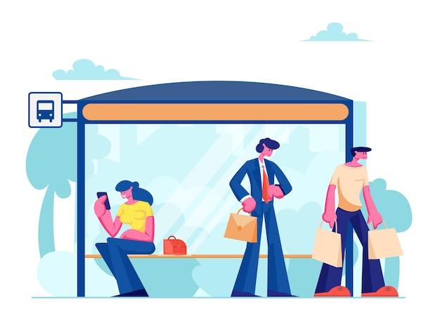 La gente sta sulla stazione degli autobus
