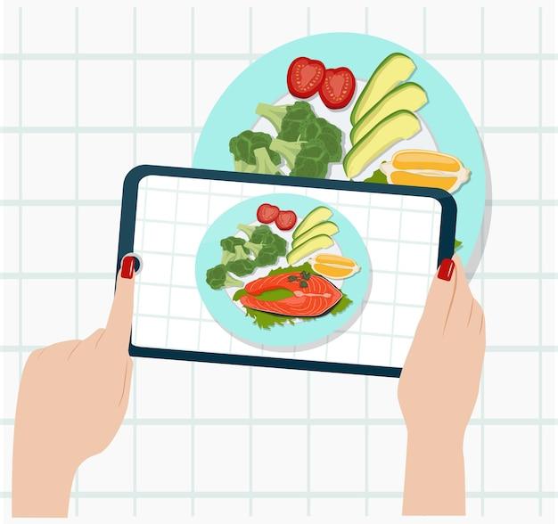 Le persone fotografano il loro cibo con il loro smartphone. una donna riprende il pranzo con una telecamera.