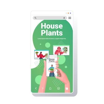 Le persone che si prendono cura delle piante d'appartamento mescolano i governanti della corsa discutendo durante la videochiamata nel browser web windows schermo dello smartphone ritratto copia spazio