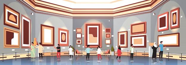 Persone turisti nella galleria d'arte moderna museo interno alla ricerca di dipinti contemporanei opere d'arte o mostre visitatori