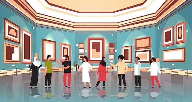 Persone turisti in galleria d'arte moderna museo interno alla ricerca di dipinti contemporanei creativi opere d'arte o mostre visitatori