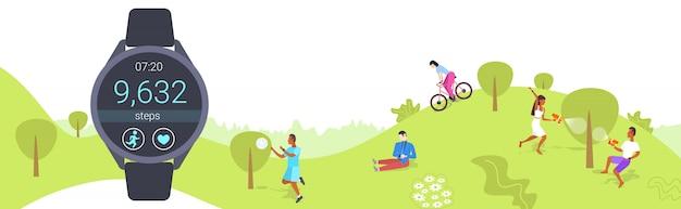 Persone che usano smart watch uomini donne che indossano attrezzature per il fitness tracker per il monitoraggio della salute digitale orologio da polso schermo attività quotidiana dati cardio smartwatch concept park paesaggio integrale