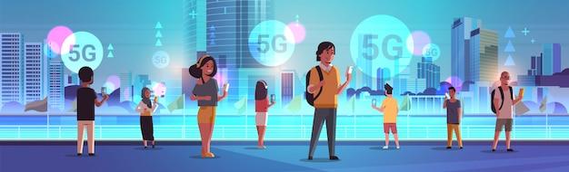 Persone che utilizzano smartphone 5g connessione al sistema wireless online quinta generazione innovativa di internet concetto mix gara uomini donne in piedi all'aperto moderno paesaggio urbano sfondo a figura intera orizzontale