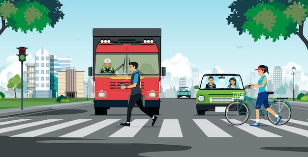 Persone che camminano su un attraversamento pedonale con un camion che si ferma a un semaforo