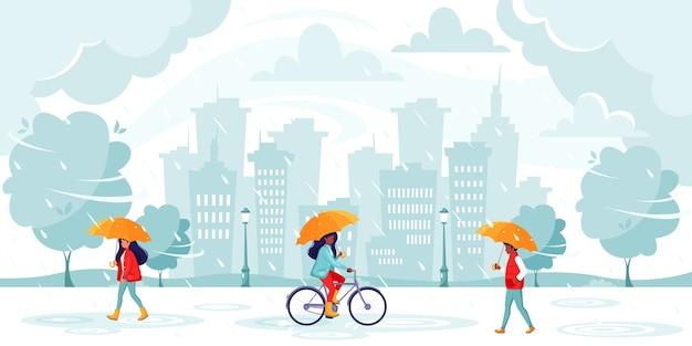 Persone che camminano sotto gli ombrelloni durante la pioggia. pioggia autunnale sullo sfondo della città.