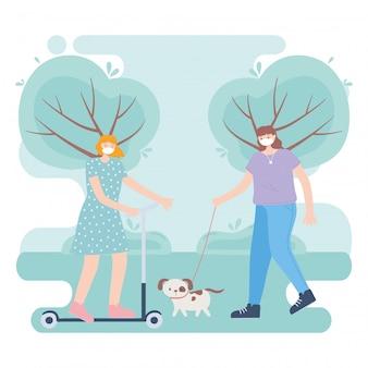 Persone con mascherina medica, donna equitazione kick scooter e ragazza che cammina con il cane nel parco