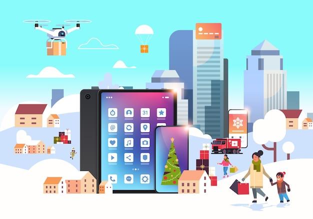 Persone con le borse della spesa che camminano all'aperto utilizzando l'app mobile online che si prepara per il paesaggio urbano invernale delle vacanze di capodanno