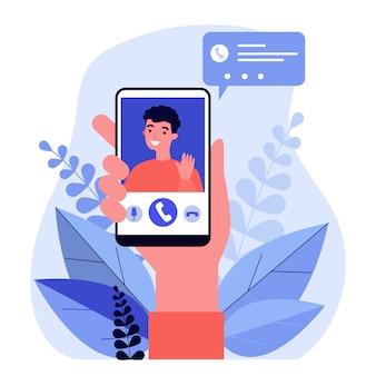 Persona in possesso di smartphone e chiamata tramite app mobile di chat video