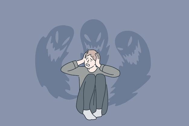 Concetto di fobie e paure interiori. giovane uomo stressato seduto toccando la testa sentendosi male con i fantasmi al muro dall'interno paure illustrazione vettoriale Vettore Premium