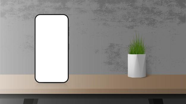 Sul tavolo c'è un telefono con uno schermo bianco. modello per la pubblicità su uno smartphone.
