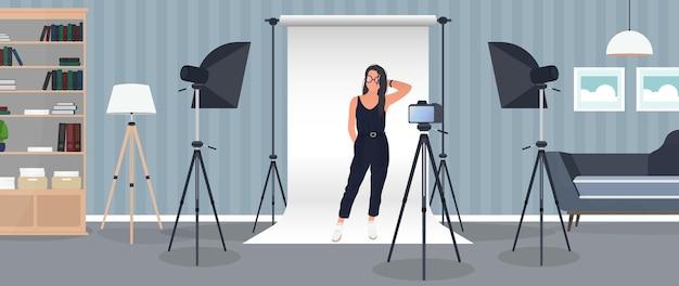 Studio fotografico ragazza in posa per la fotocamera. sfondo di tela bianca su treppiedi.