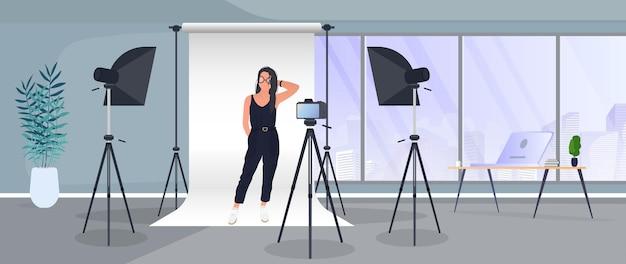 Studio fotografico vettoriale. ragazza in posa per la fotocamera. sfondo di tela bianca su treppiedi. fotocamera su treppiede, softbox. studio fotografico professionale.