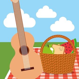 Cestino di vimini da picnic cibo e chitarra sulla collina