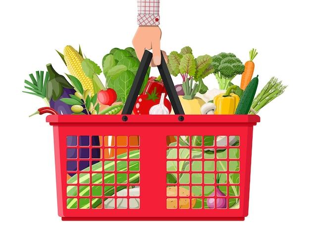 Cestino della spesa in plastica pieno di verdure in un cestino