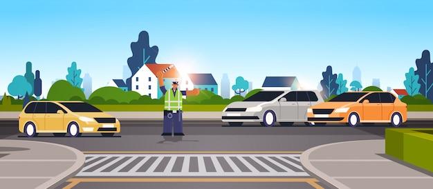 Ispettore di polizia sulla strada con le automobili facendo uso dell'ufficiale di poliziotto afroamericano del bastone da passeggio in orizzontale integrale piano di concetto uniforme di servizio di norme di sicurezza stradale