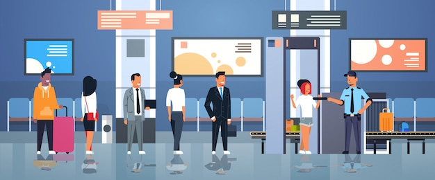 Ufficiale di polizia che controlla passeggeri e bagagli all'interno del terminale del dipartimento di controllo di sicurezza dell'aeroporto dello scanner completo del corpo dei raggi x del metal detector