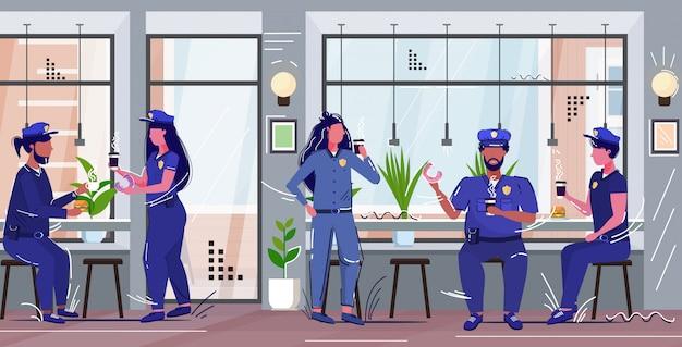 Gli agenti di polizia mangiando ciambelle bevendo caffè poliziotti e poliziotte in uniforme pranzando autorità di sicurezza giustizia diritto servizio concetto moderno bar interno schizzo a figura intera