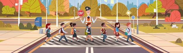 Guardia del poliziotto aiuta il gruppo di bambini delle scuole che attraversano la strada