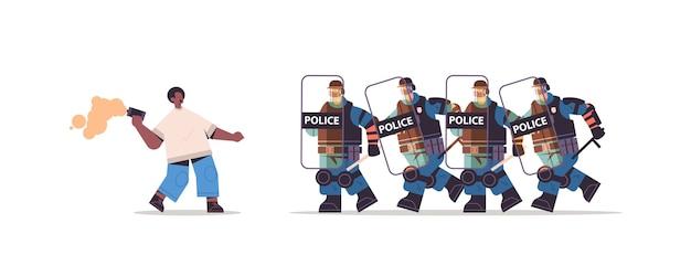 Poliziotti in completo equipaggiamento tattico polizia antisommossa che attacca manifestante afroamericano durante scontri dimostrazione protesta
