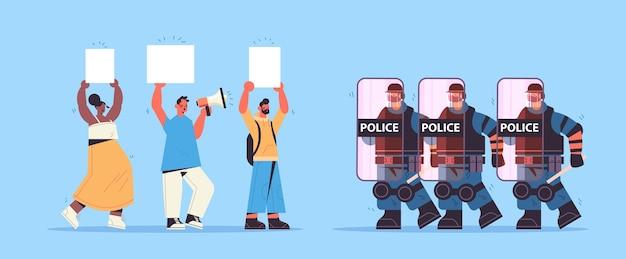 Poliziotti in completo equipaggiamento tattico agenti di polizia antisommossa che attaccano i manifestanti di strada con cartelli durante gli scontri