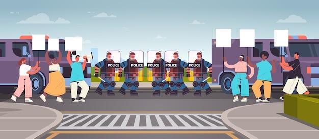 Poliziotti in completo equipaggiamento tattico agenti di polizia antisommossa che controllano i manifestanti di strada con cartelli durante gli scontri dimostrazione protesta rivolte di massa