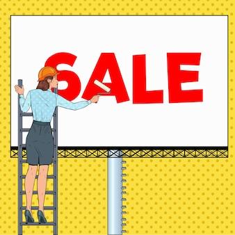 Donna di affari di pop art in casco con il tabellone per le affissioni. lavoratore di sesso femminile che applica banner di vendita. concetto di pubblicità.