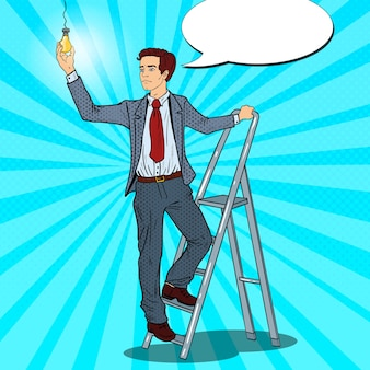 Uomo d'affari di pop art con scala e lampadina.