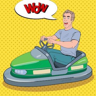 Pop art eccitato uomo equitazione paraurti auto alla fiera del divertimento. guy in dodgem al parco dei divertimenti.