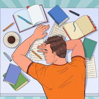 Pop art esaurito studente maschio che dorme sulla scrivania con libri di testo. uomo stanco che prepara per l'esame. Vettore Premium