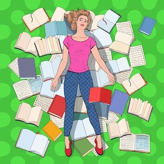 Pop art studente esausto sdraiato sul pavimento tra i libri. giovane donna sovraccarica che prepara per gli esami. concetto di educazione.