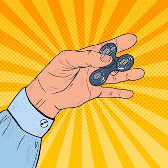 Pop art mano che gioca con fidget spinner