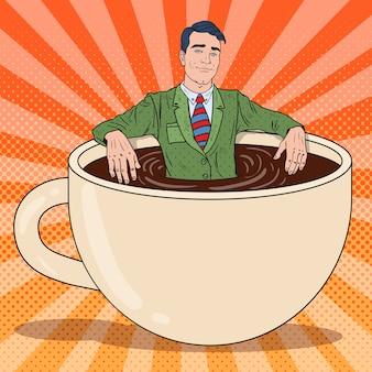 Uomo d'affari felice di pop art che si rilassa nella tazza di caffè. pausa di lavoro.