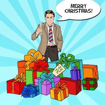 Pop art uomo felice con grandi scatole regalo e bicchiere di champagne.