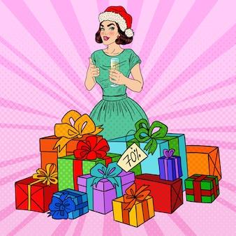 Pop art donna felice in cappello della santa con grandi scatole regalo e bicchiere di champagne.
